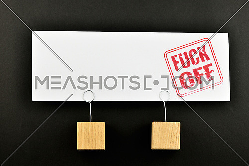 Fuck off red rude stamnp on one big white paper note with two wooden holders isolated on black paper background for presentation