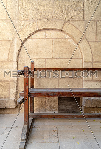 Wooden garden bench with background of stone bricks wall with arched niche at House of Egyptian Architecture historical building, Cairo, Egypt