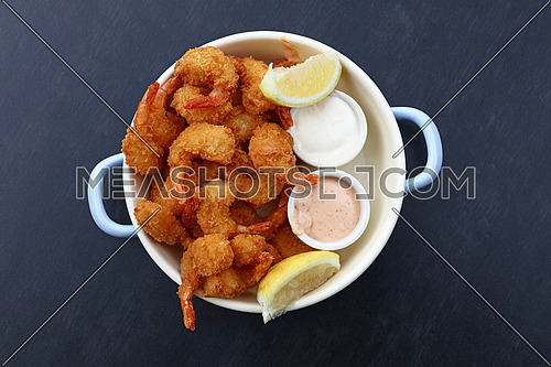 Close up portion of battered and breaded shrimps with dipping sauces served in cooking pot over blue table copy space, elevated top view, directly above