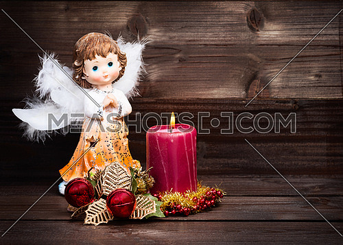 Christmas greeting card with candle and angels on wooden background.