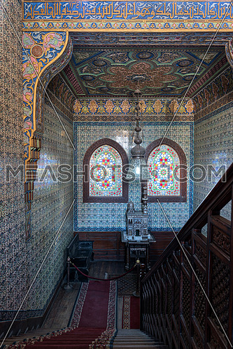 Descending wooden staircase with decorated engraved wooden balustrade, Turkish floral blue pattern ceramic tiles wall, ornate colorful ceiling, two arched wooden windows with colored stained glass at the residence hall at Manial Palace of Prince Mohammed Ali