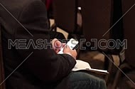 Close up shot from behind for man using a mobile device at a meeting.