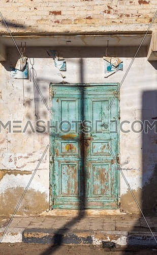Closed wooden weathered door and shabby old grunge stone wall on abandoned district