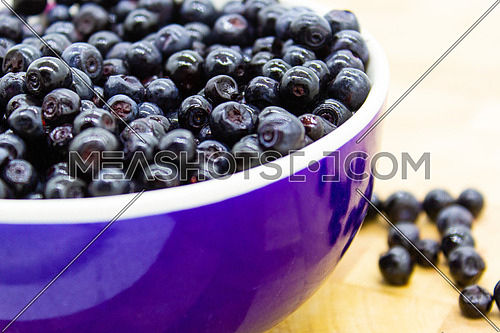 Large group of blueberries in a round bowl on a wooden table