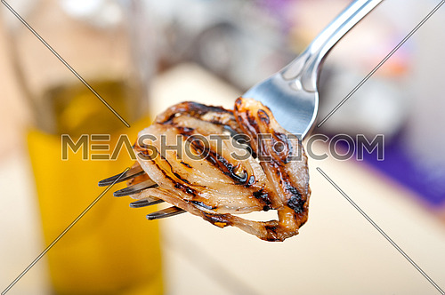 grilled onion on a fork macro close up