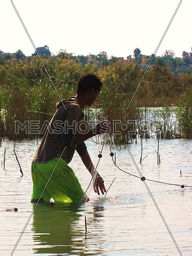 A fishier boy gathering the fishing net in the lake