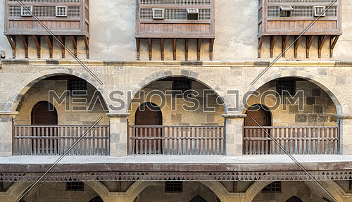 Front view of three arches with interleaved wooden balustrades at the arcades of the courtyard of caravansary (Wikala) of Bazaraa, Cairo, Egyp