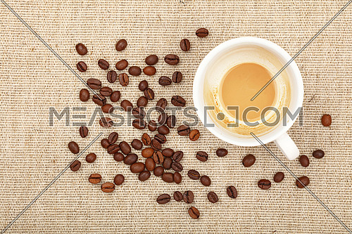 One empty finished white cup of latte cappuccino and roasted coffee beans on background of linen canvas