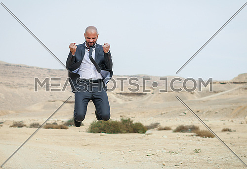 Man jumping high - celebrating victory - in desert
