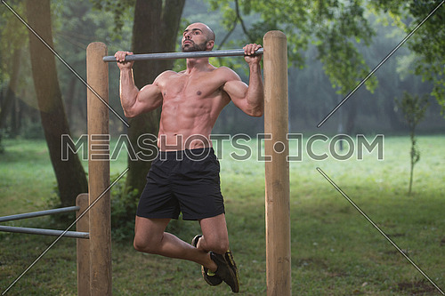 Muscular Built Young Athlete Working Out In An Outdoor Gym - Doing Chin-Ups