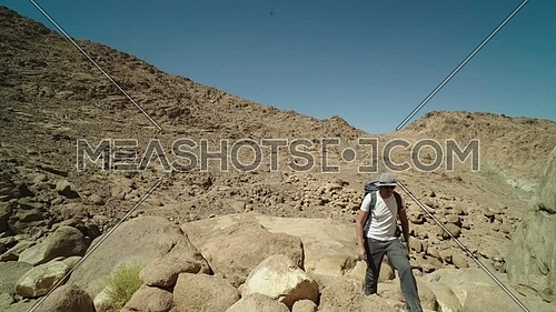 Follow shot for a male tourist wearing a grey cap and travel backpack explore Sinai Mountain for wadi Freij at day.