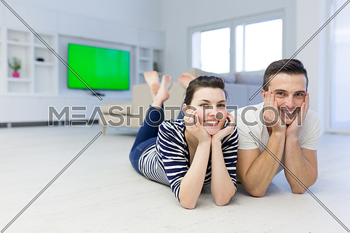 Lovely couple enjoying free time lying on the floor in their living room at home