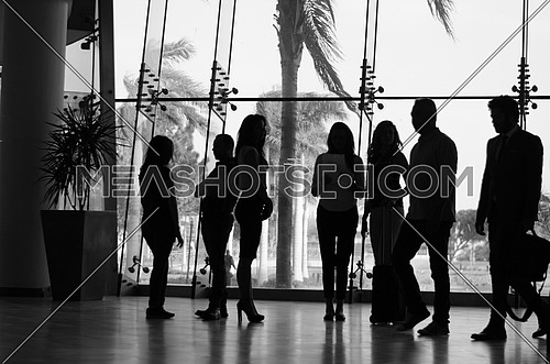 A business group standing in a room talking finance