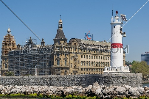 White beacon at the Bosphorus with Haydarpasha Railway Terminal at the background situated in south of the Port of Haydarpasha, Kadikoy, Istanbul, Turkey