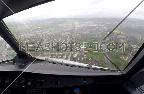 inside cockpit shot  while flying towards runway at rainy day