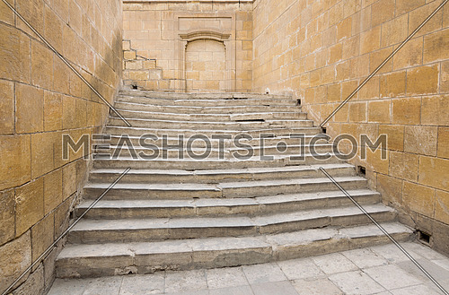 Ancient wide stone staircase, framed by stone walls from three sides