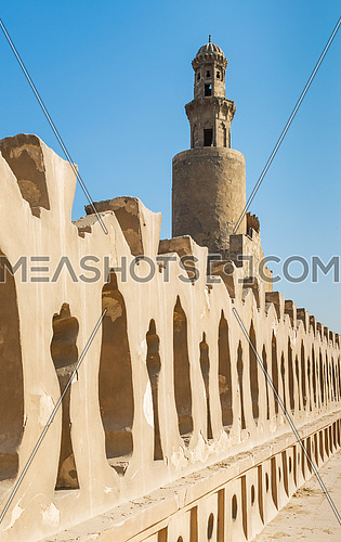 Stone bricks old decorated fence of Mosque of Ibn Tulun revealing minaret of the mosque, Medieval Cairo, Egypt
