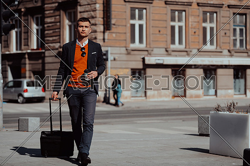 Portrait of a tourist man carrying a suitcase and holding a cup of coffee while walking outdoors on the street. Tourism concept.