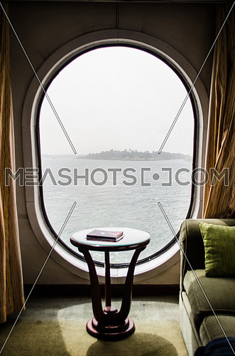 A big window in a ship and a coach in a ship room