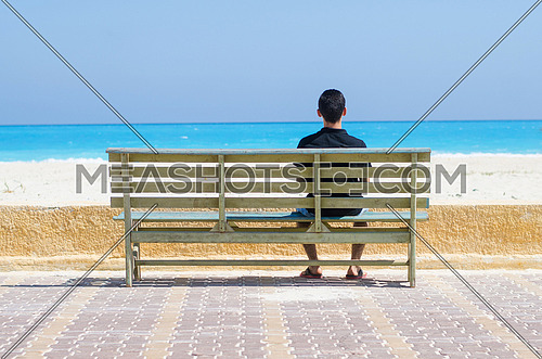 a lonely young man sitting on a bench by the sea