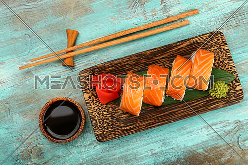 Close up one set of six Philadelphia sushi rolls with raw salmon served on palm wood plate on blue table, elevated top view, directly above
