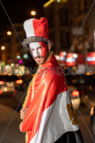 Egyptian football supporter in the street with Egyptian flag dressed, painting his face with Egyptian Flag and wearing a hat at night