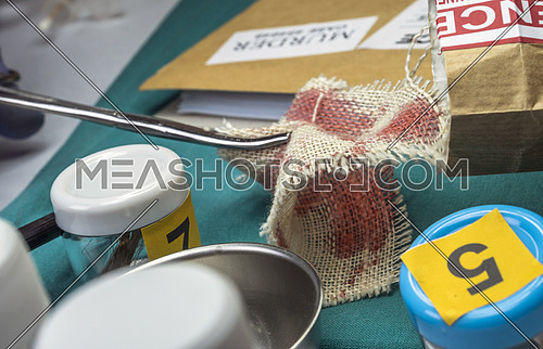 Police specialist examines piece of cloth stained with blood belonging to the victim of murder, conceptual image