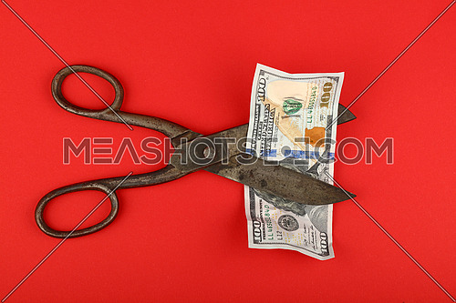US financial crisis, decline of American economy and dollar exchange rate illustrated, old vintage scissors cut one hundred dollars banknote at over red background, elevated view