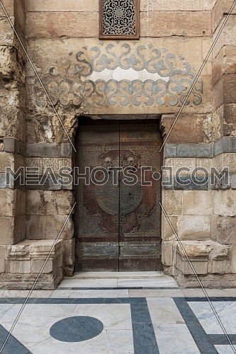Stone bricks wall and wooden decorated copper plated door leading to Sultan Barquq mosque, Al-Moez Street, Old Cairo, Egypt
