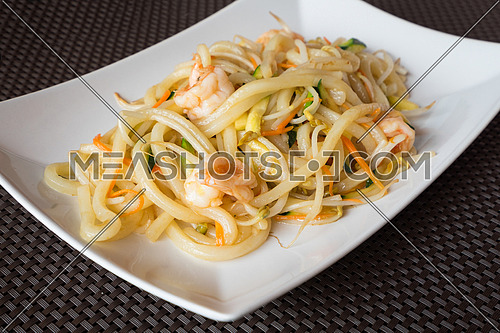 delicious japanese food yaki udon, noodles with seafood,shrips and vegetables,white plate on dark backgroung.