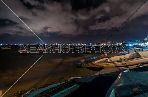 Fixed shot for sea shore showing fishing boats at alexandria at night
