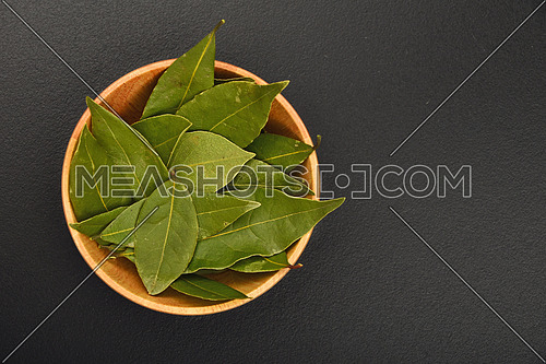 Wooden bowl of bay laurel leaves on black chalkboard background