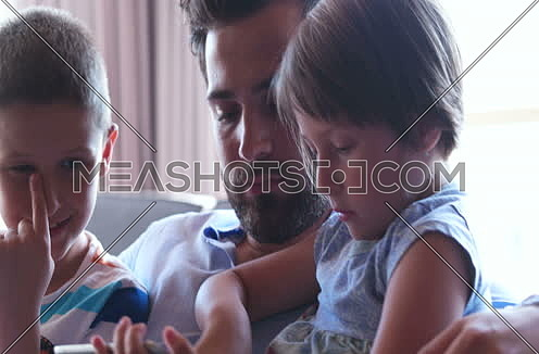 Young Father With Two Kids using technology in modern apartment at day