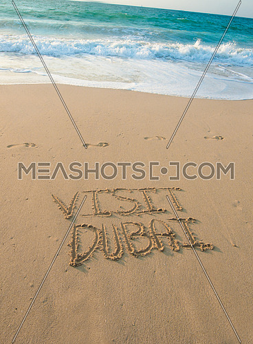 in the picture at the beach  written on the sand Visit Dubai