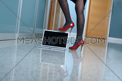 business woman stand with shoe on modern laptop