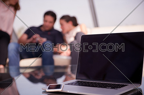 modern laptop with empty screen at modern office interior, business people group in background working together