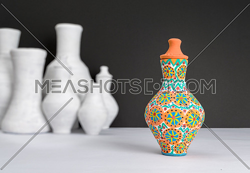Still life of one decorated painted colorful pottery vase on background of blurred group of white vases, white table and black wall