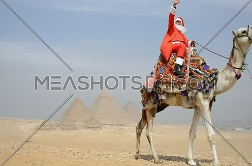 long shot for santa riding a camel at the pyramids at day