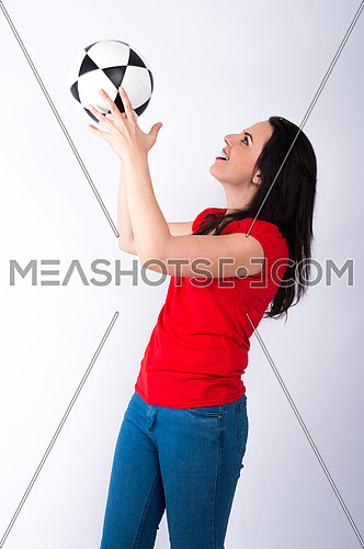 Portrait of a beautiful young woman carrying in her hand football