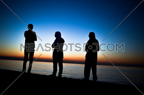 3 friends standing at the beach during sunset magic golden hour