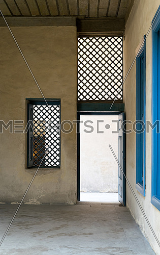 Blue vintage wooden window with interleaved wooden grid (mashrabiya) and blue wooden door with plaster yellow wall