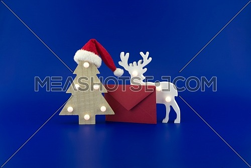 Christmas tree with a Santa hat on top next to a red envelope for greetings and stylized wooden reindeer on a festive blue background. New Year and Christmas greeting season concept