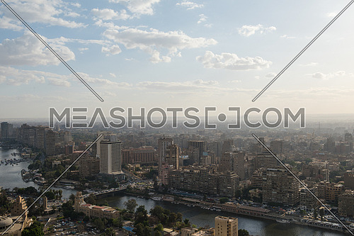 aerial view of modern Greater Cairo city downtown with Nile with pyramids in the horizon on a beautiful sunny day with blue sky and clouds capital of Egypt