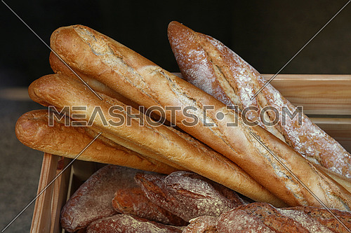Close up several fresh French baguette bread buns on retail display of bakery store, high angle view