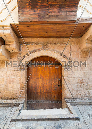 Exterior of aged stone house with weathered walls and arched wooden door, in old town