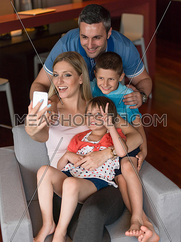 Happy family siting on sofa and using cell phone for video call  at home