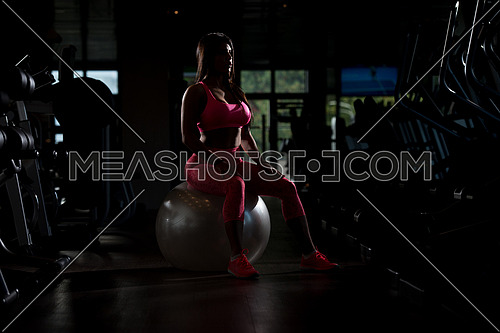 Young Mexican Woman Resting On Ball After Working Out In Fitness Center