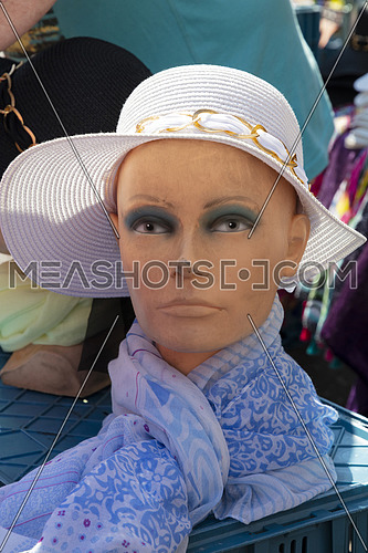 Woman mannequin with hat and scarf at open market retail display