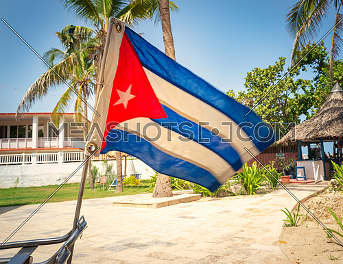 Cuban flag placed in the back of the bike with gardens and beach background, during the sunny day