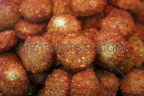 Traditional oriental Middle Eastern meal dish of deep fried ready to eat falafel balls on retail market display, close up